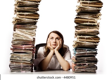 Young adult female sits between two high stacks of file folders with a defeated look on her face.