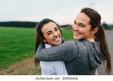 Young Adult Females arms around each other laughing
