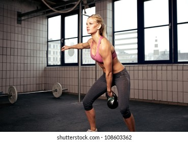 Young adult fitness woman doing swing exercise with a kettlebell as a part of a fitness workout
