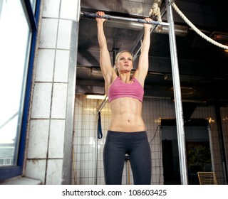 Young adult fitness woman preparing to do pull ups in pull up bar.