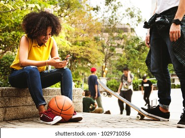 Young adult friends chilling at the park using smartphones and skateboarding youth culture concept