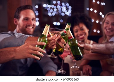 Young adult friends make a toast at a house party, close up