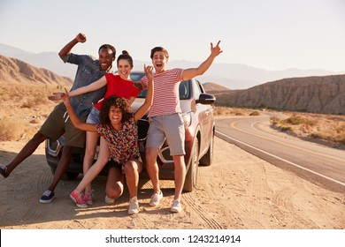 Young adult friends on road trip have fun posing by the car