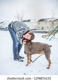 A young adult gentleman taking his dog out for a walk, bending down to give his best friend a hug in the snow by the neighborhood park.