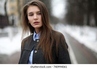 Young adult girl in coat on the street in the city