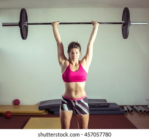 Young adult girl doing heavy weightlifting during gym active exercise. Strong willpower. Toned image.