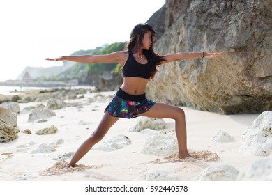 Young adult girl doing yoga at the beach in Bali Indonesia