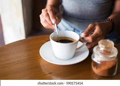 Young adult girl enjoying coffee and breakfast at a cafe