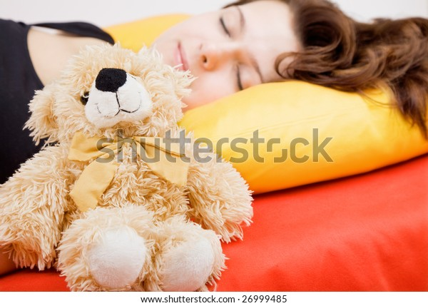 Young adult girl lying in bed with teddy bear