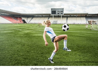 Young adult girl playing football or soccer, kicking a ball with her knee Beautiful blond woman in a sports suit stand on her legs on a green grass football field against empty stadium and scoreboard