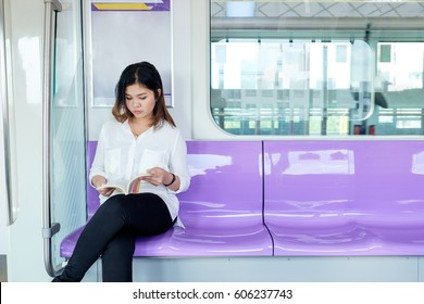 young adult girl reading a book on metro train transit, sky train Purple Line in Thailand