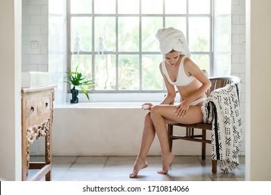 Junge erwachsene Mädchen mit Handtuch auf dem Kopf sitzend auf Stuhl in weißem Bad, mit weicher natürlicher Creme auf den Beinen, Haut-und Körperpflege Verfahren