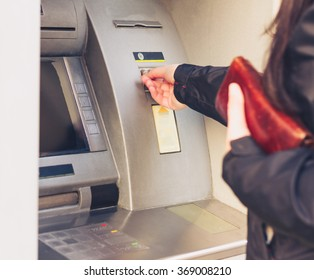 Young adult girl withdraws money from an ATM. Selective focus on her right hand. Warm tone.