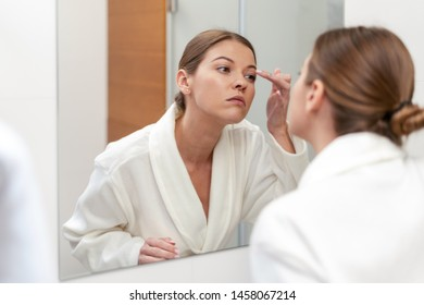 Young adult and good-looking woman in white bathrobe standing in bright light bathroom with mirror. She looking at her reflection, holding hand near face