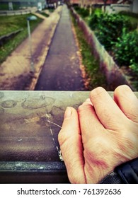 young adult hand affected by arthritis on a metallic bridge railing