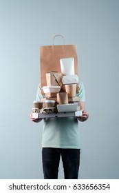 Young adult holding pizza box, take-out food containers, coffee cups in holder and paper bag, close-up. Light grey background. Delivery man.
