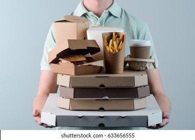 Young adult holding several pizzas, hamburger in paper box, take-out coffee cups in holder and French fries, close-up. Light grey background. Fast food.