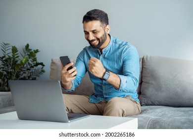 Young adult indian business man screaming proud cheering with excitement reading great news on smartphone celebrating victory and success sitting front of laptop computer working at home office