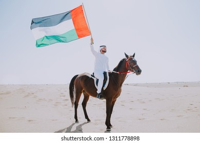 Young adult with Kandura, the emirates traditional clothes, riding his horse in the desert