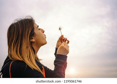 Young adult latin woman blowing dandelion flower outdoors