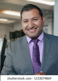 Young adult latino american walking out of a building in his well put together business attire smiling at the camera after a successful business meeting or convention.