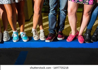 Young Adult legs and feet standing together on blue curb