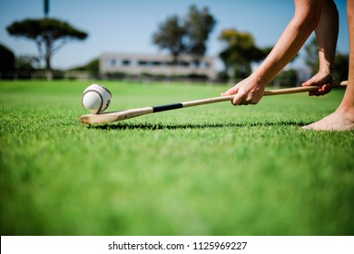 df442a36c2194 Young adult lifting up slither on a hurl playing traditional irish sport  hurling at the park