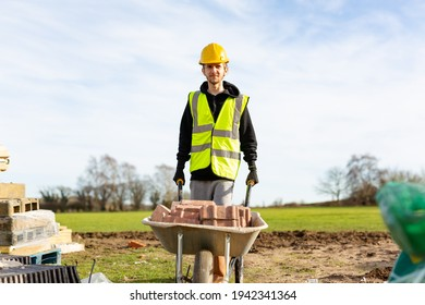 A young adult male builder wearing a high visibility vest and hard hat pushing a wheelbarrow full of bricks while on a building site