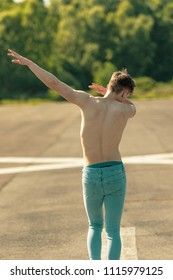 Young adult male dabbing shirtless on a warm summer's day