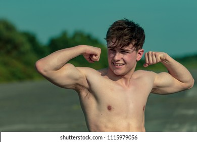 Young adult male flexing his muscles shirtless on a warm summer's day