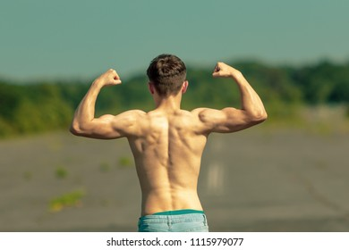 Young adult male flexing his muscles viewed from the back on a warm summer's day