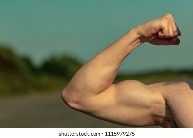 Young adult male flexing his bicep muscles shirtless on a warm summer's day