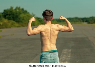 Young adult male flexing his back muscles on a warm summer's day