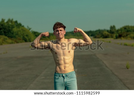 Young adult male flexing his muscles on a warm summer's day