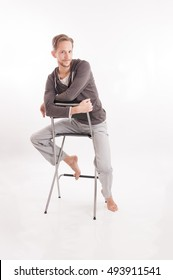 Young adult male sitting on a bar chair barefoot isolated on white background.