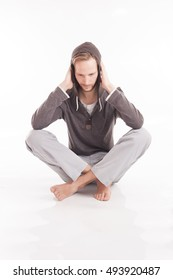 Young adult male sitting on the floor barefoot with his legs crossed and covering his ears isolated on white background.