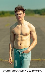 Young adult male standing outside shirtless on a warm summer's day