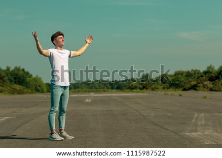 Young adult male standing outside with arms outstretched enjoying the sunshine