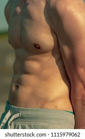 Young adult male standing shirtless outside on a warm summer's day