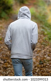 A young adult male walking alone outside on an autumn day