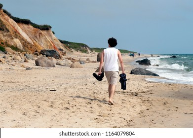 Young adult male walking barefoot carring snadles and shirt on sandy Moshup Beach with cliffs on the Island of Martha's Vineyard in Massachusetts.