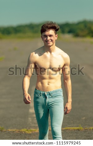 Young adult male walking forward shirtless on a warm summer's day