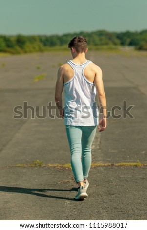 Young adult male walking outside in the sunshine