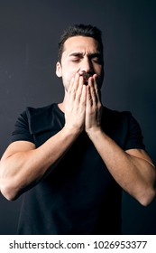 Young adult man with beard and moustache wearing a black t-shirt, feeling sleepy, studio portrait against black background