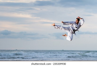 Young adult man with black belt jumping to practice Marcial Arts kick on the beach. Real shot, not a photomontage.