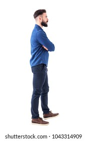 Young adult man in blue denim shirt walking and looking away with crossed arms. Full body isolated on white background.
