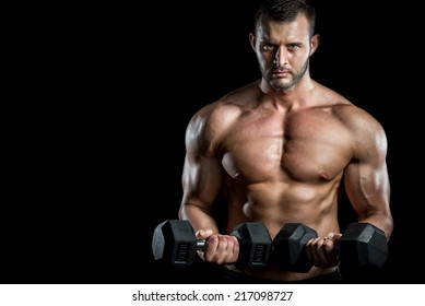 Young adult man doing barbell press in gym. Black background. Gym training workout.