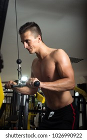 Young adult man doing cable pull down triceps exercise in gym
