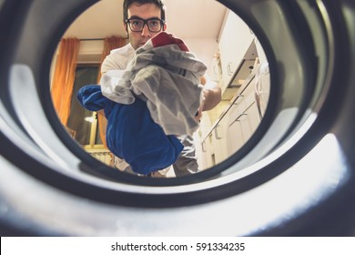 Young adult man doing chores. Cheerful man putting dirty clothes on the washing machine. Unusual portrait taken from the washing machine.