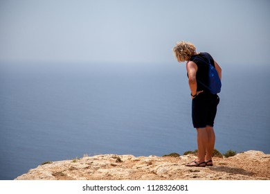 Young adult man dressed in summer style looks out over the sea horizon from a clifftop